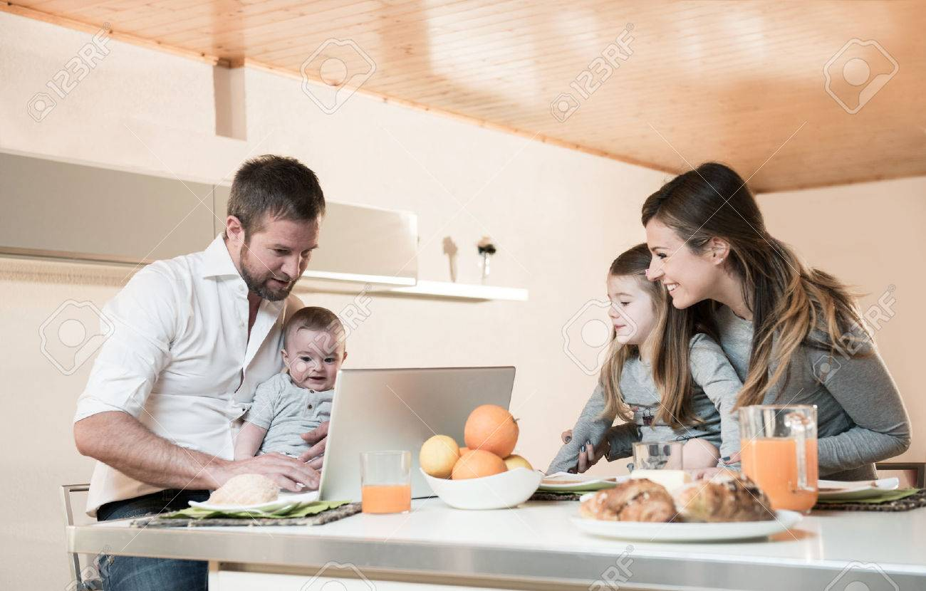 Happy family having breakfast , father on laptop with baby - 31559001