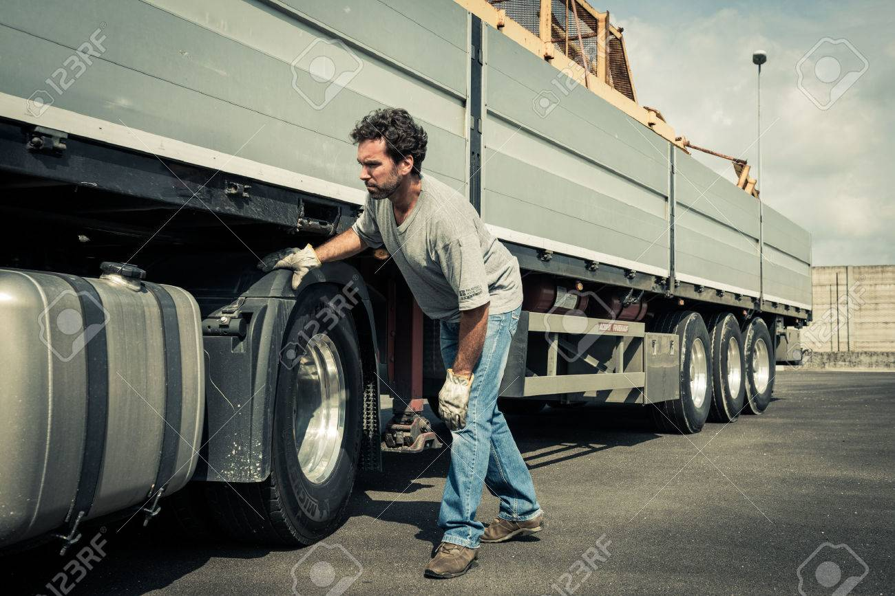 Truck driver working on truck tires - 33894242