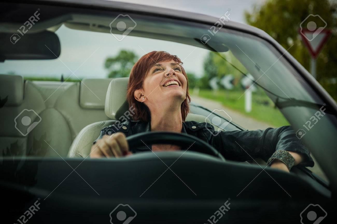 Woman enjoying driving her convertible car - 33894773