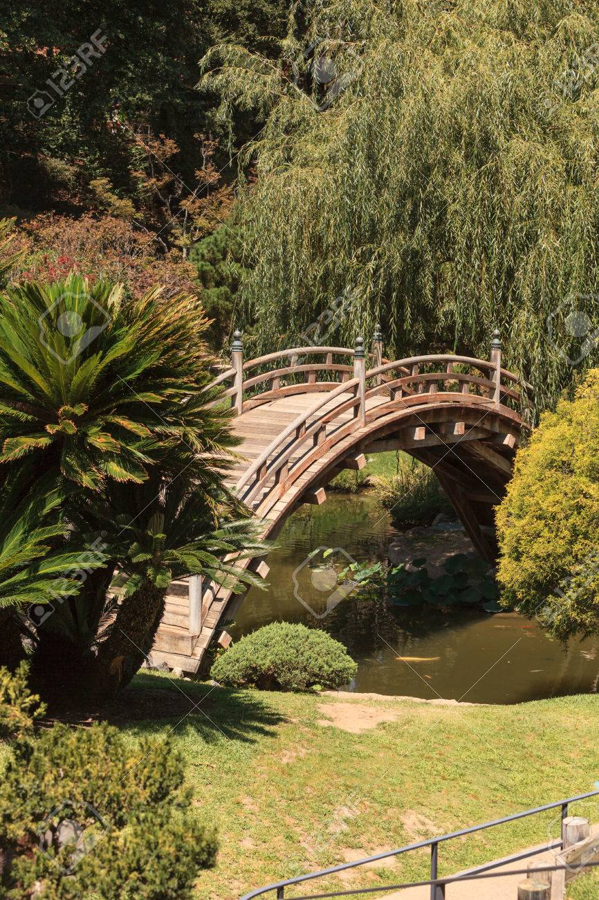 Japanese Garden With A Wood Bridge, Statues, Koi Pond And Water Lilies.  Stock