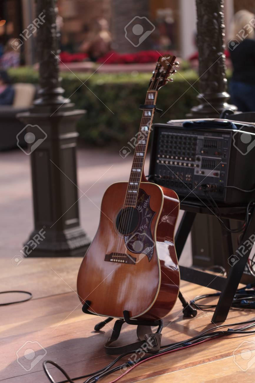 Six String Acoustic Guitar Sits On A Stand On An Outdoor Stage