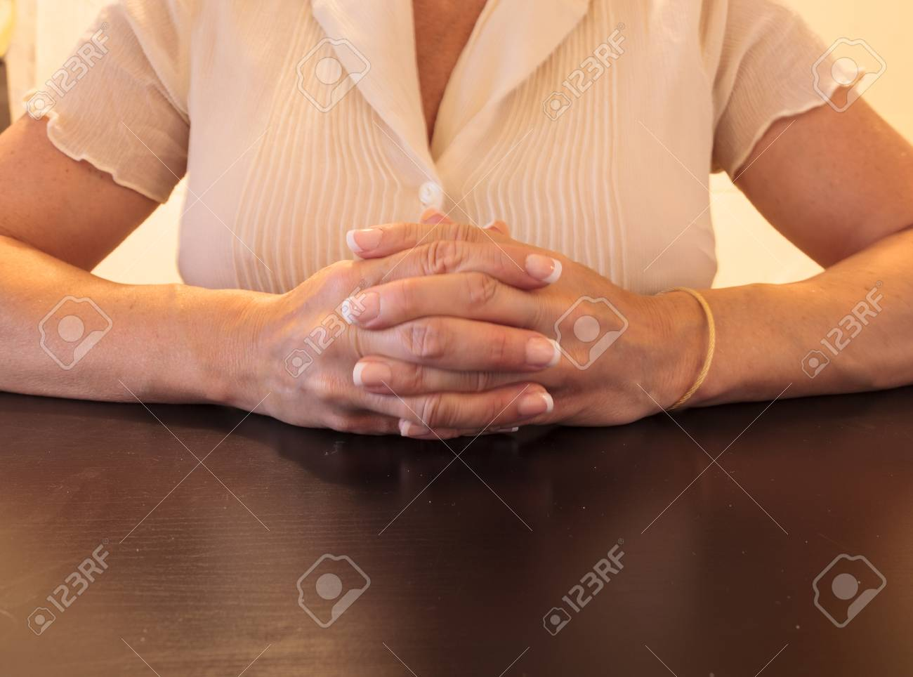 Female With Manicured Nails Clasping Hands At A Desk In An Office ...