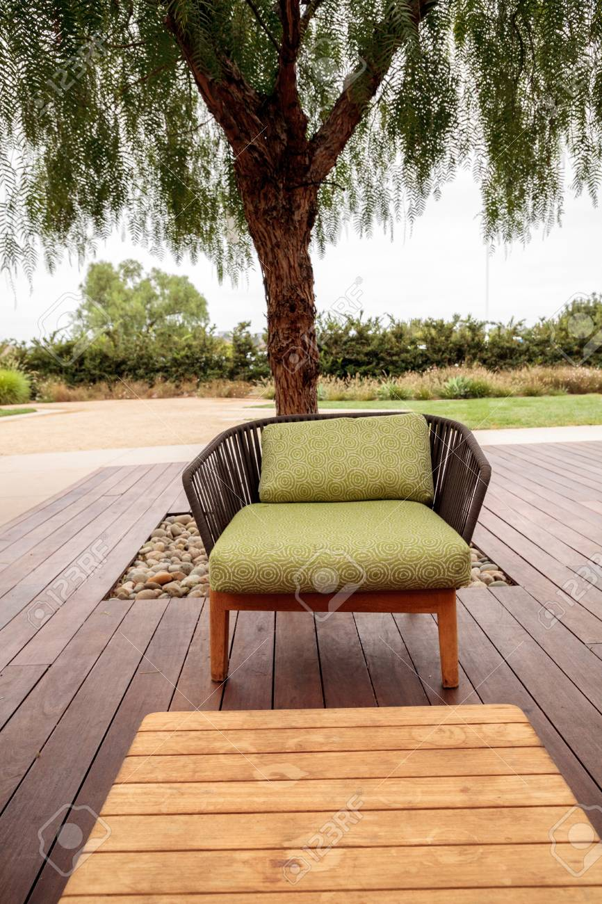 Stock photo wood patio lounge chairs with green cushions in the backyard with green grass in the summer