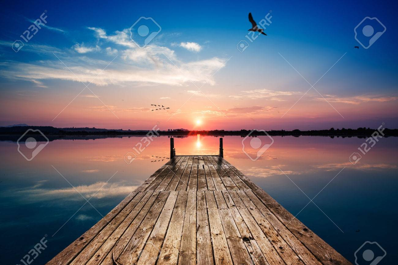 Perspective view of a wooden pier on the pond at sunset with perfectly specular reflection - 53959199
