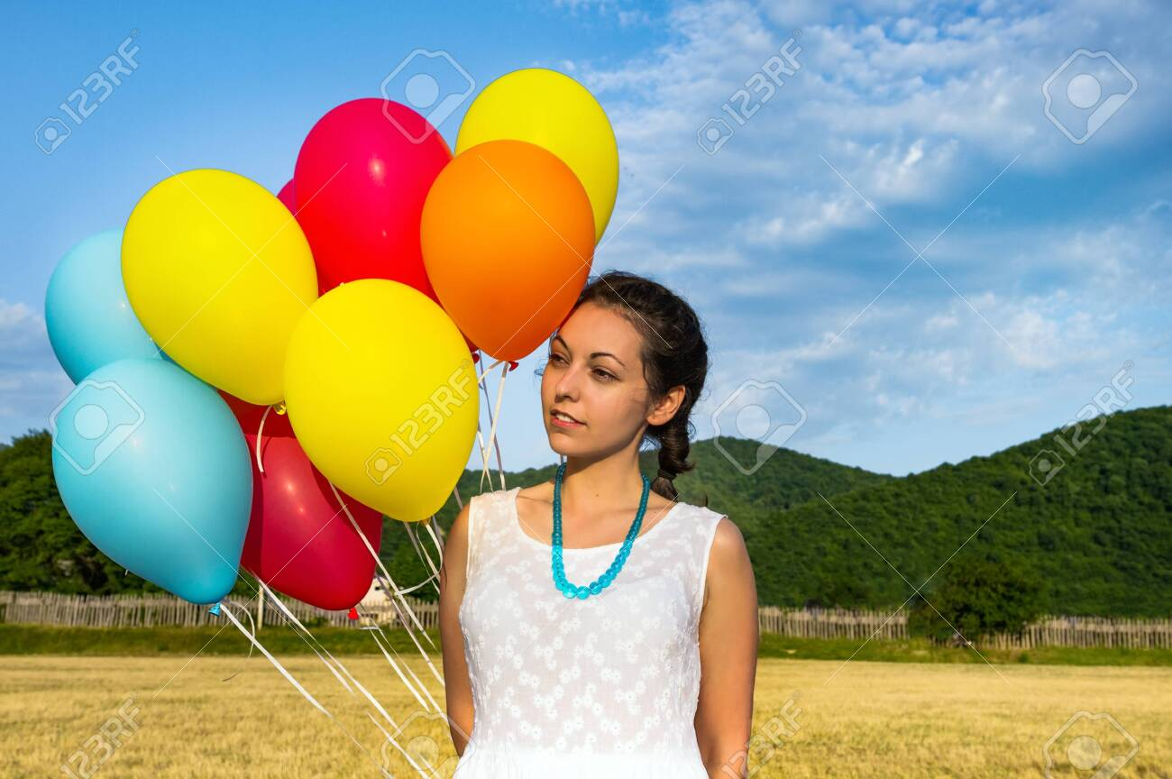 Cute young woman in white dress with balloons in her hands. The concept of freedom and joy. Close up - 126400472