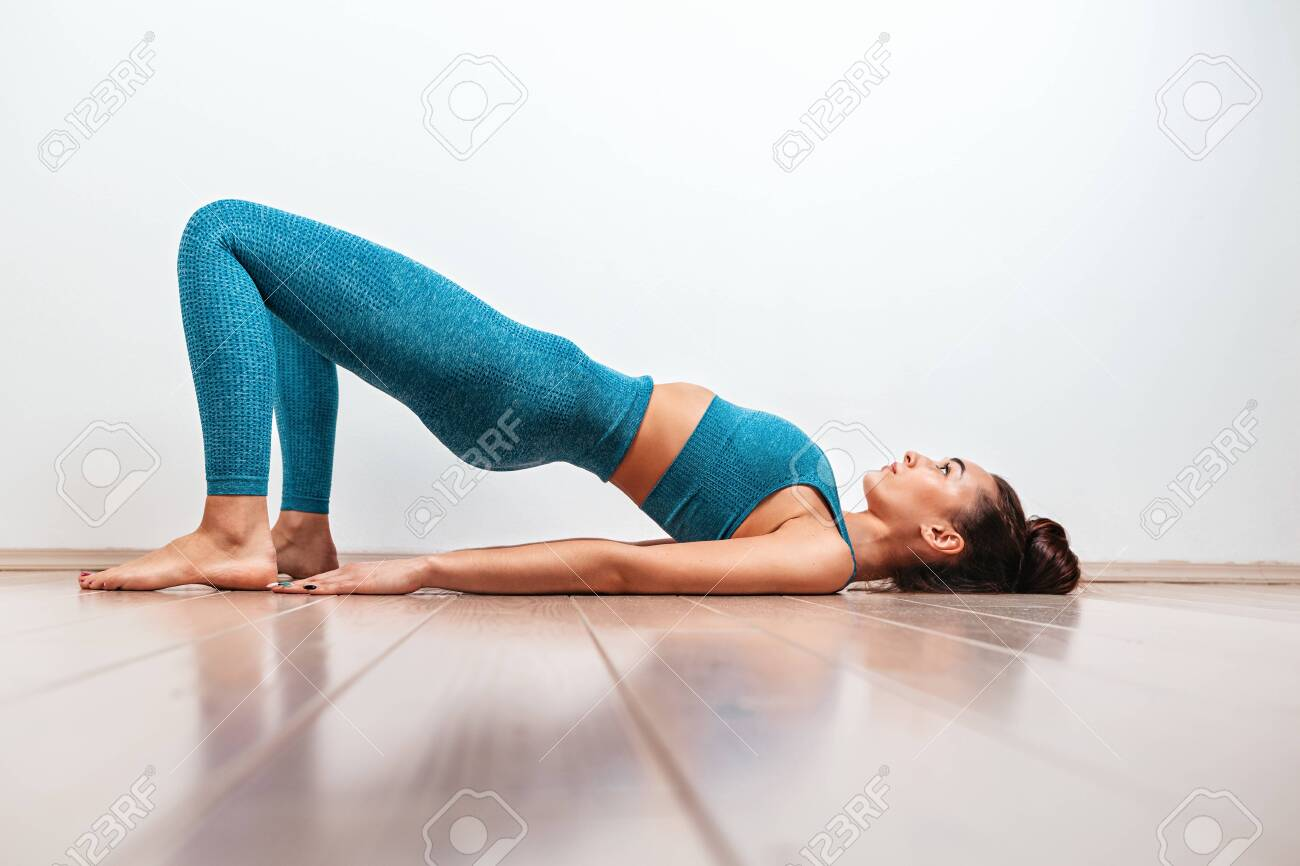 Yoga and sports concept. A young Caucasian woman is engaged in warm-up, performing the exercise bridge. White background in the background. Copy - 139291525