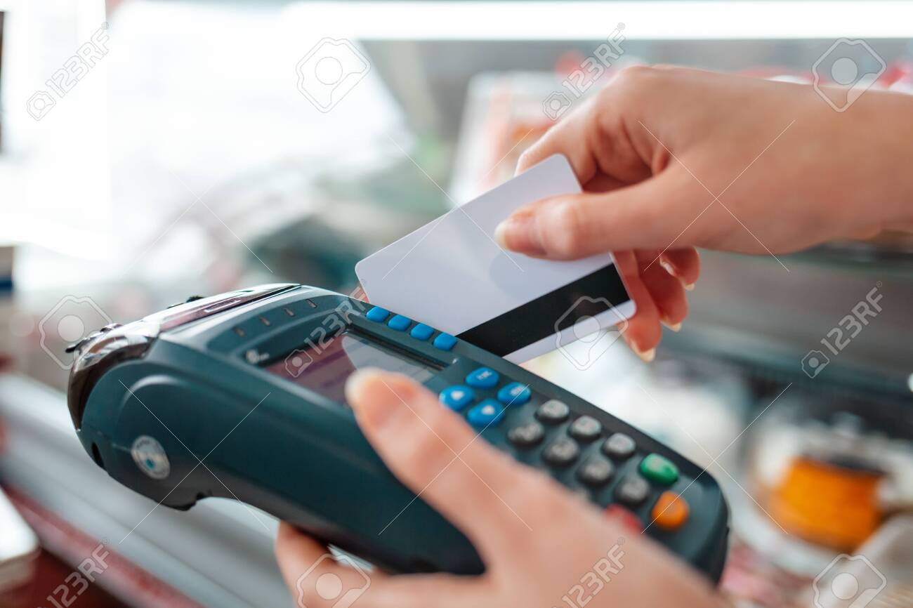 The woman swipes a Bank card through the payment machine to complete the purchase payment. Hands close-up. NFC concept, business and banking operations. - 142949466