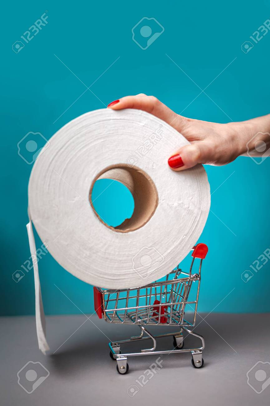 A woman's hand with a red manicure puts a roll of toilet paper on a small cart. Turquoise background. Close up. Concept of coronovirus, panic shopping and hygiene. - 145857551