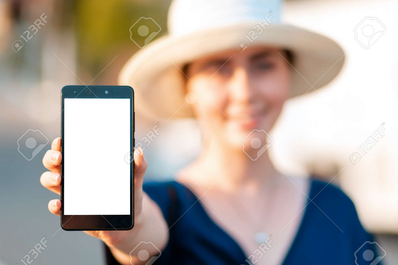 A woman in straw hat holds a smartphone in her hand, hand close-up. Portrait in a blur. Concept of modern technologies, business and applications for the phone. - 153692288