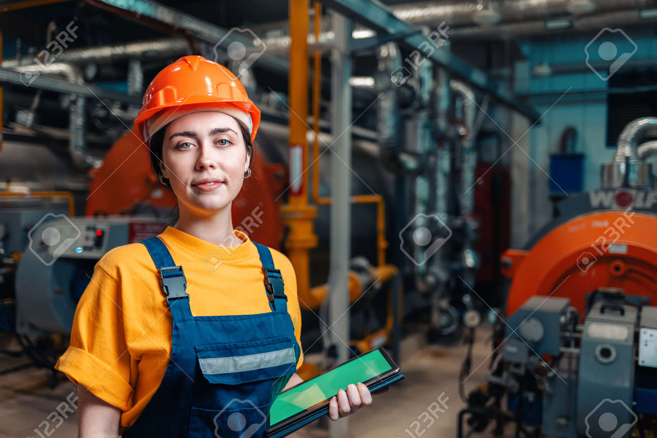 Industrial production concept. Portrait of a female engineer in uniform and helmet with a tablet in her hand. In the background-boiler equipment. - 166057718