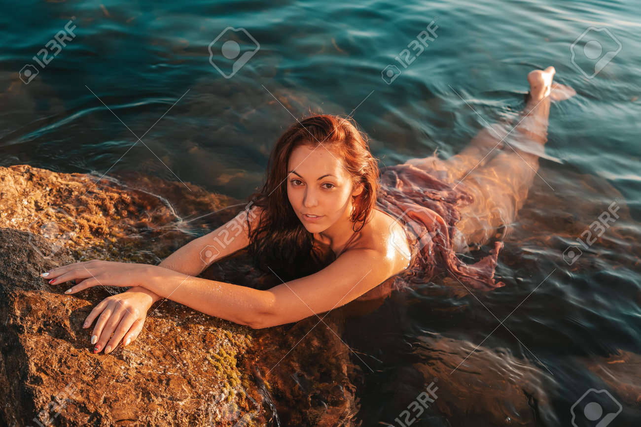 Sexy tanned woman in lingerie bathes in the sea and rests on the coastal rocks. The sea in the background. View from the top. - 167196292