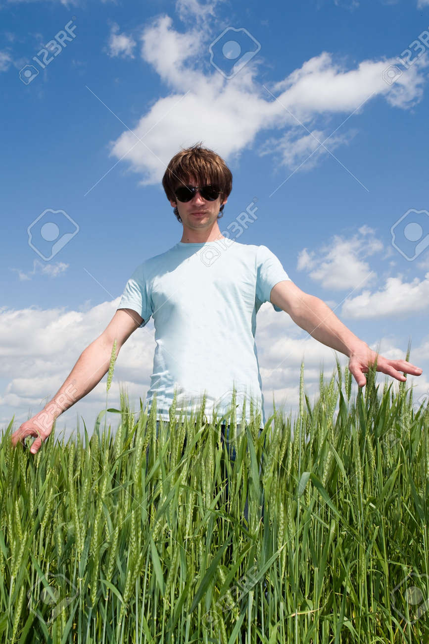 young man touches the hand green ears of rye Stock Photo - 3170385