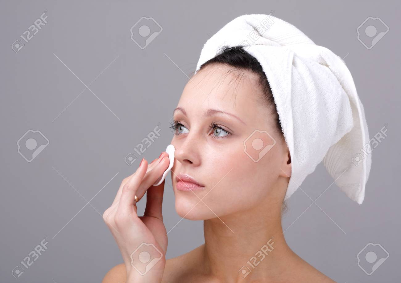 Demake up. Young attractive woman cleaning face. Stock Photo - 4341357