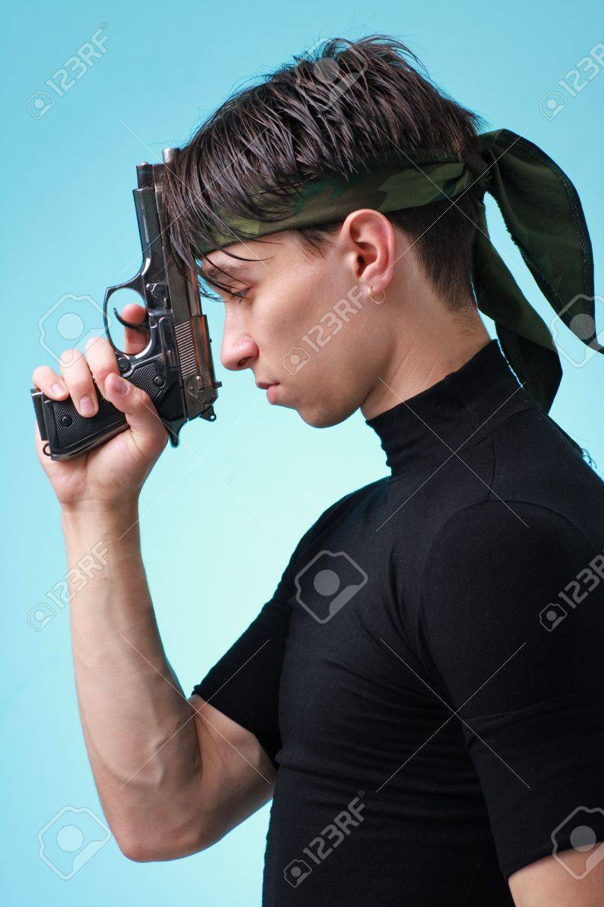 Man with gun close up on a blue background. Stock Photo - 6467032