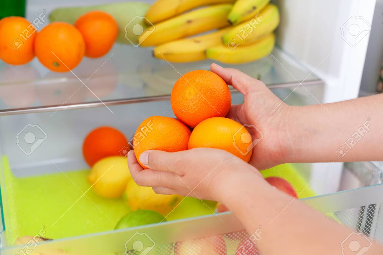 Woman getting some fresh oranges from fridge. Close up. - 126428726