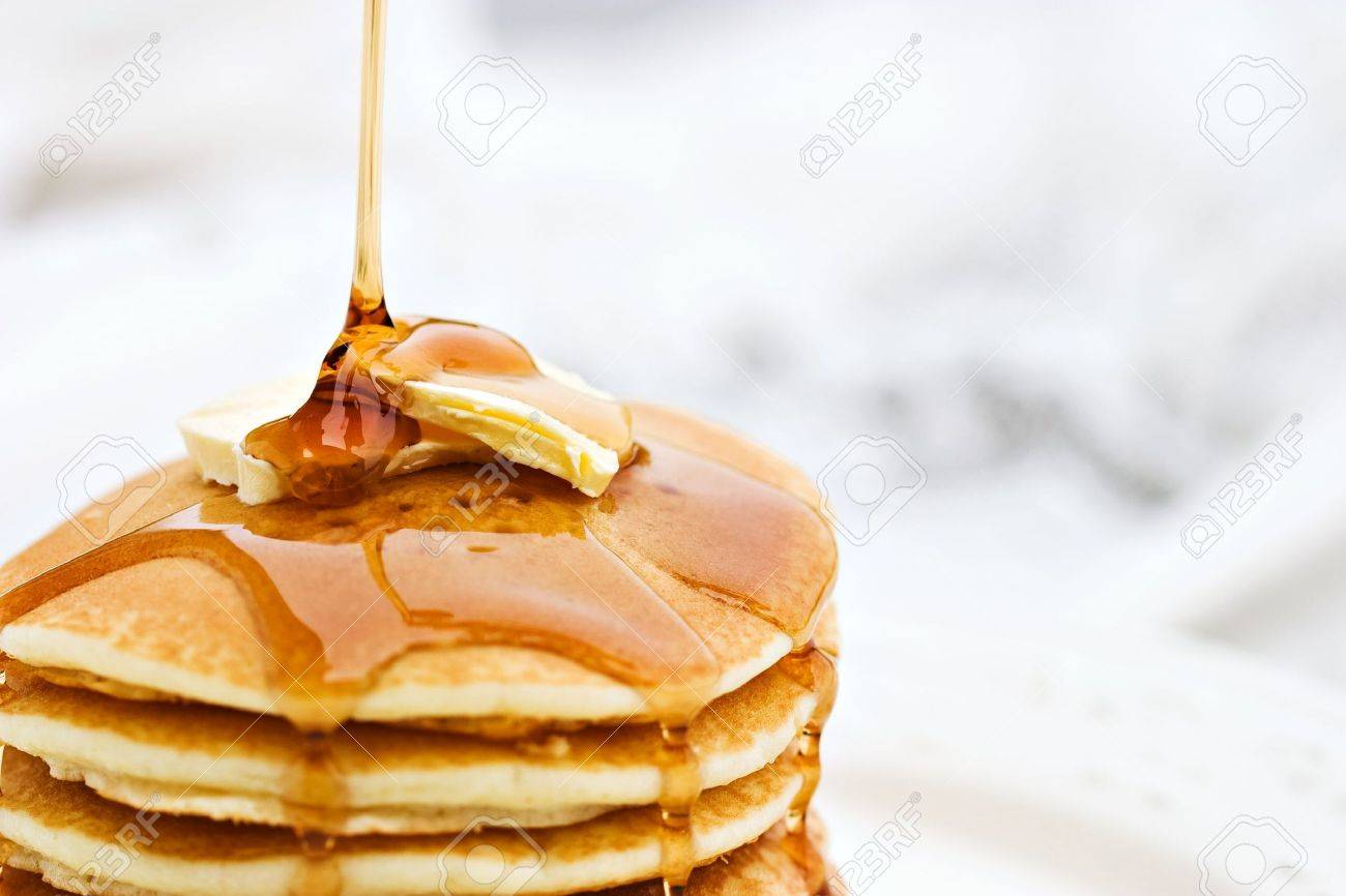 Maple syrup pouring onto pancakes. Shallow DOF with focus on syrup and butter. - 5272504