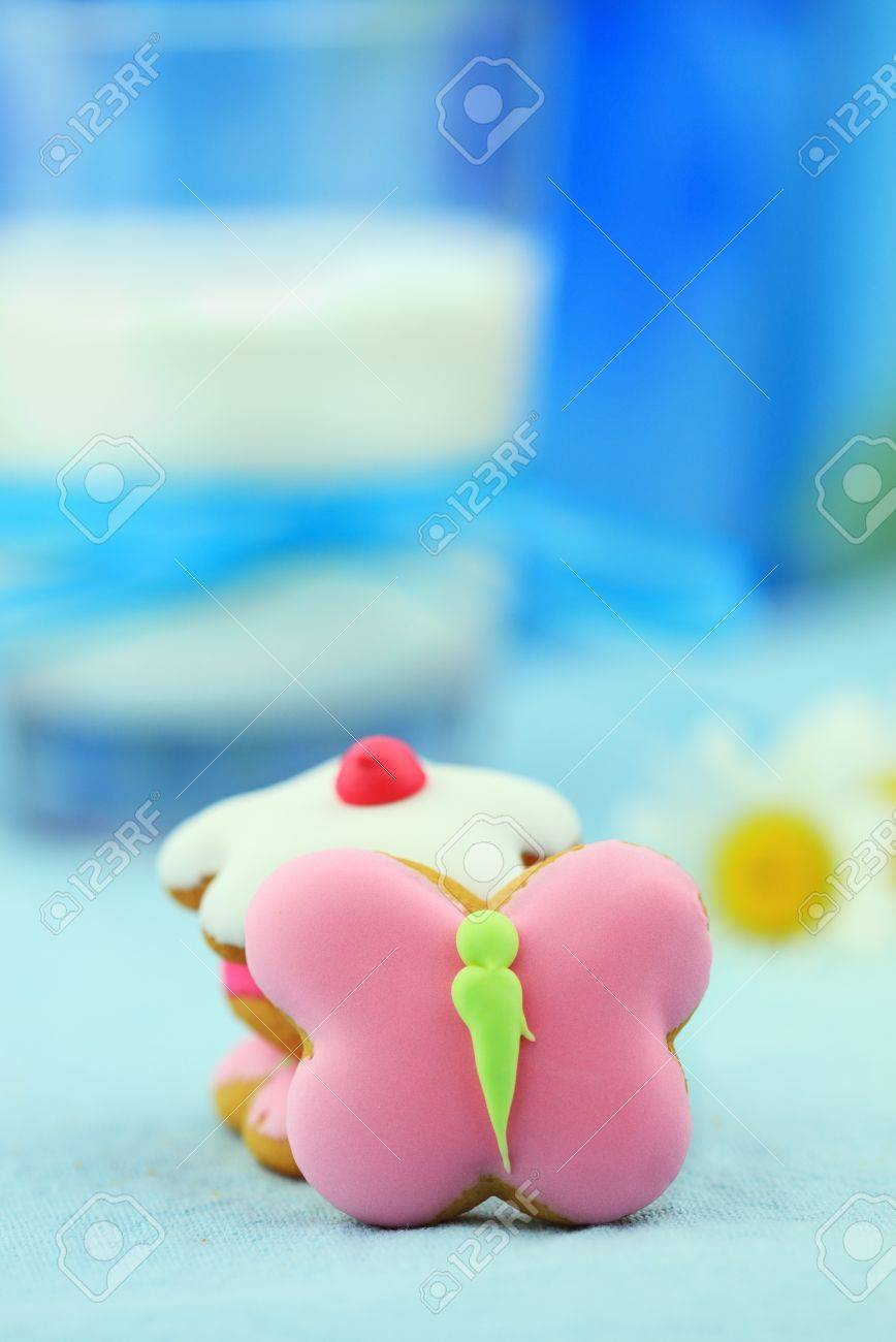 Cute butterfly and flower shaped cookies with glass of milk and daisies in the background. Selective focus on butterfly cookie with extreme shallow DOF. Some blur on lower portion. Stock Photo - 8530292