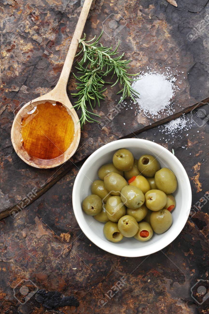 Spanish olives with olive oil, rosemary, sea salt and olive on a rustic slate background. Stock Photo - 9957928