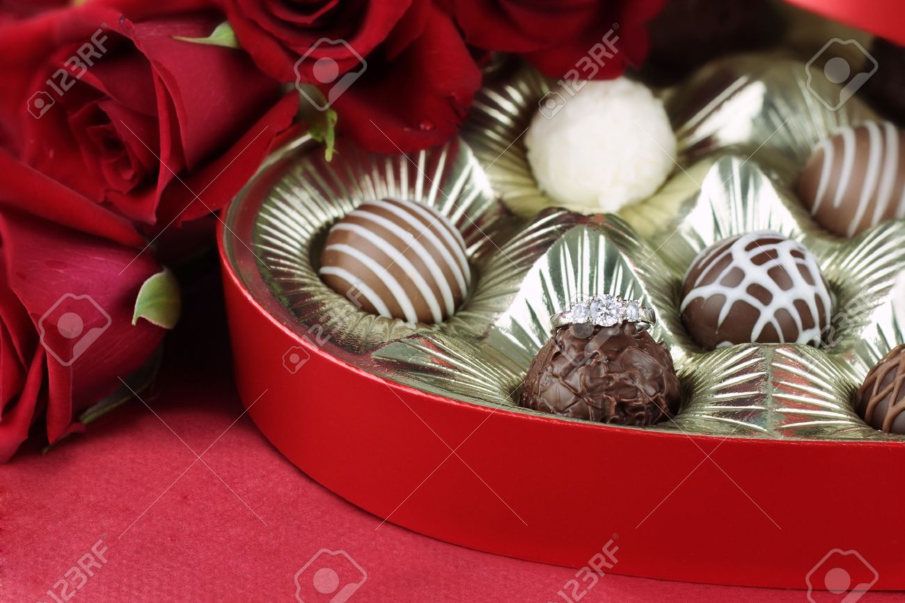 Diamond engagement inside of a heart shaped box of chocolate truffles with red roses. Selective focus on diamond ring with soft blurred background. Stock Photo - 11738543