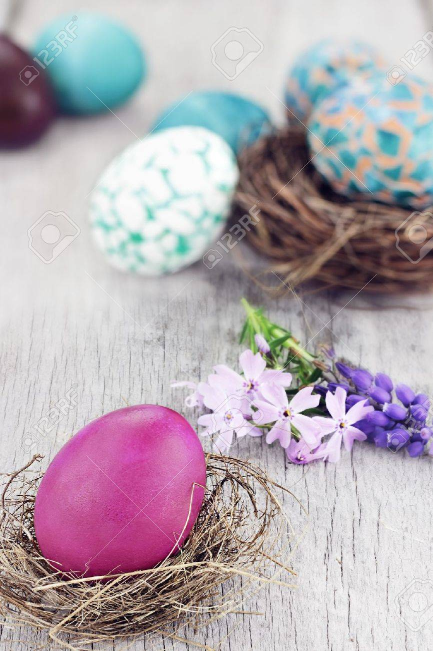 Beautiful Easter egg in a small nest with spring flowers and more eggs in background. Selective focus on egg in foreground. Stock Photo - 12865959