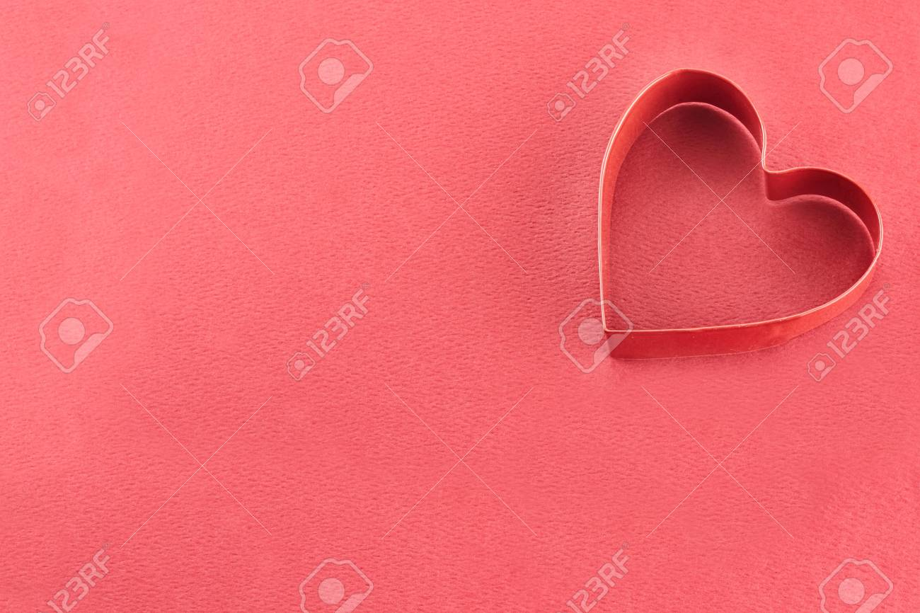 Heart shaped cookie cutter over a red background. Stock Photo - 17103153