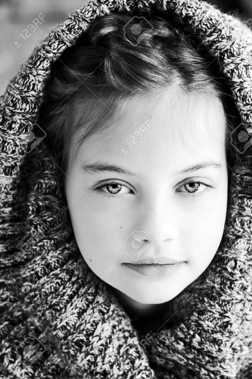 Black and white studio shot of a beautiful young girl in a hooded sweater with shallow
