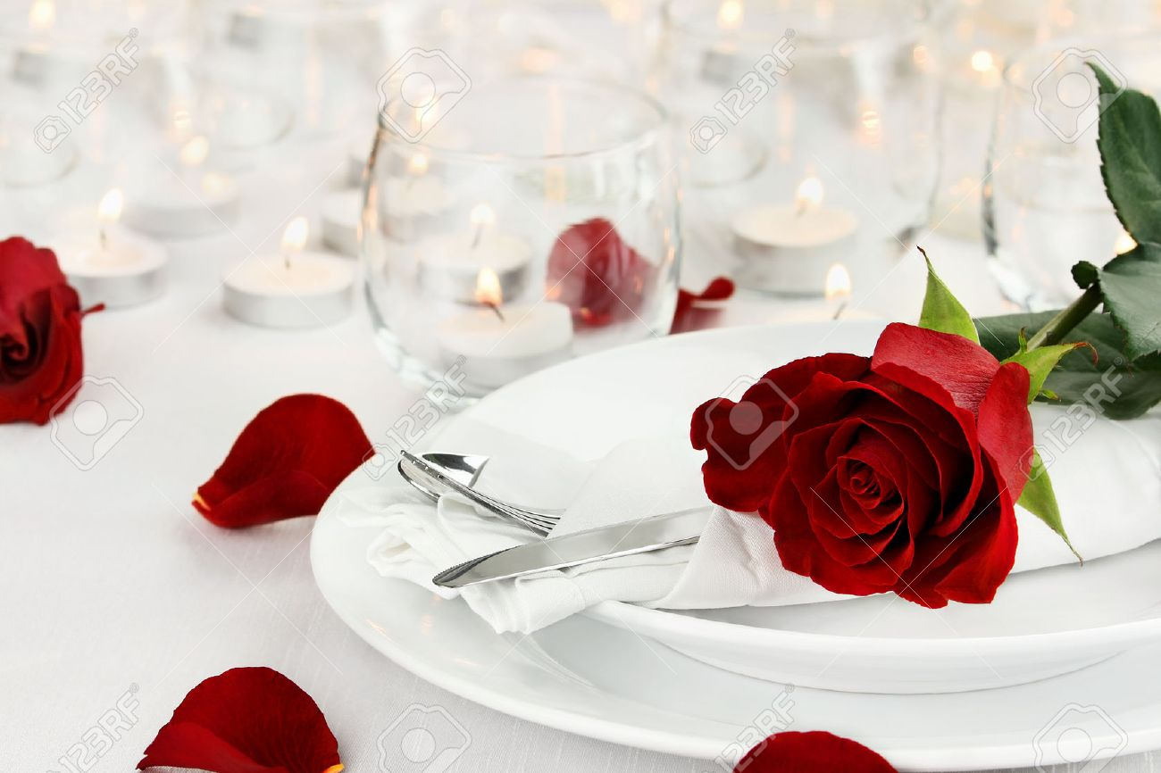Romantic table setting with long stem red rose and candles burning in the background. Shallow depth of field with selective focus on rose. Stock Photo - 50817352