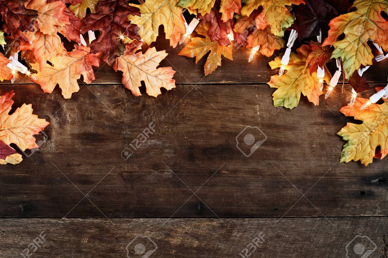 Rustic Fall Background Of Autumn Leaves And Decorative Lights Over A Barn Wood