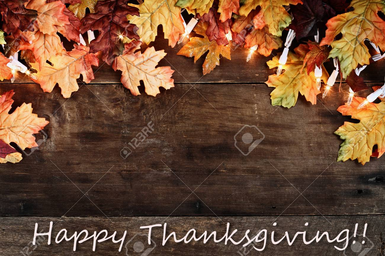 Rustic Fall Background Of Autumn Leaves And Decorative Lights With Happy Thanksgiving Text Over A