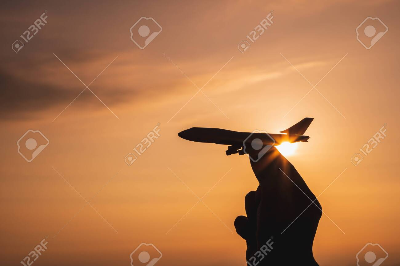 A hand holding a toy plane Go to the sky with sunset light - 142227698