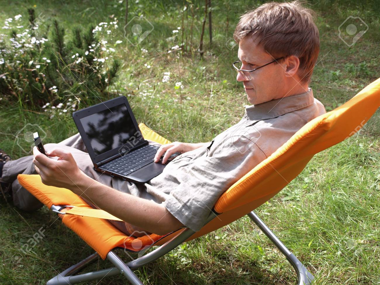 Young man with netbook and cell phone in hand Stock Photo - 11743466