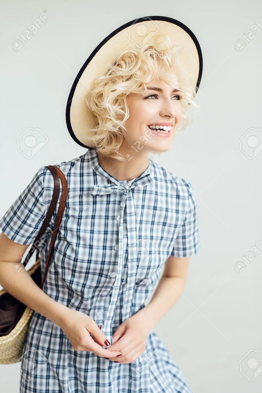 Archivio Fotografico - Ragazza felice con i capelli bianchi in un cappello  e con una borsa sulla sua spalla ab0901f6c02d