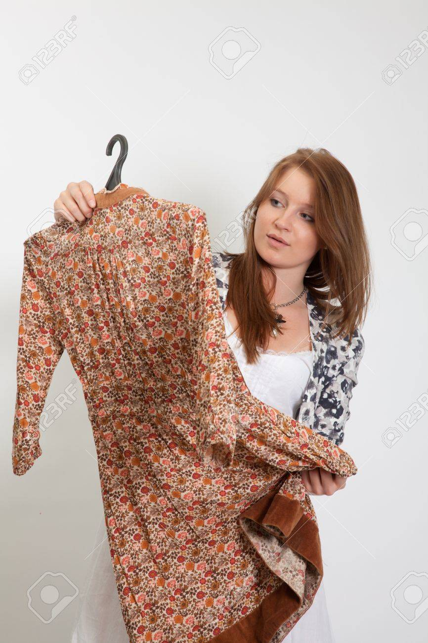 The girl considers a dress, intending it to buy - 9378387