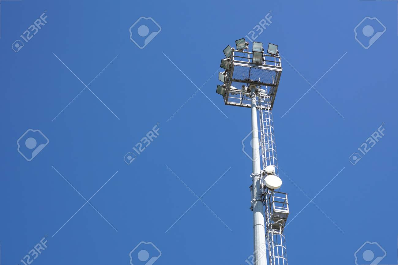 Outdoor stadium lights and telecommunication tower against daytime blue sky.  Single row of bulbs with 48db0af534d7f
