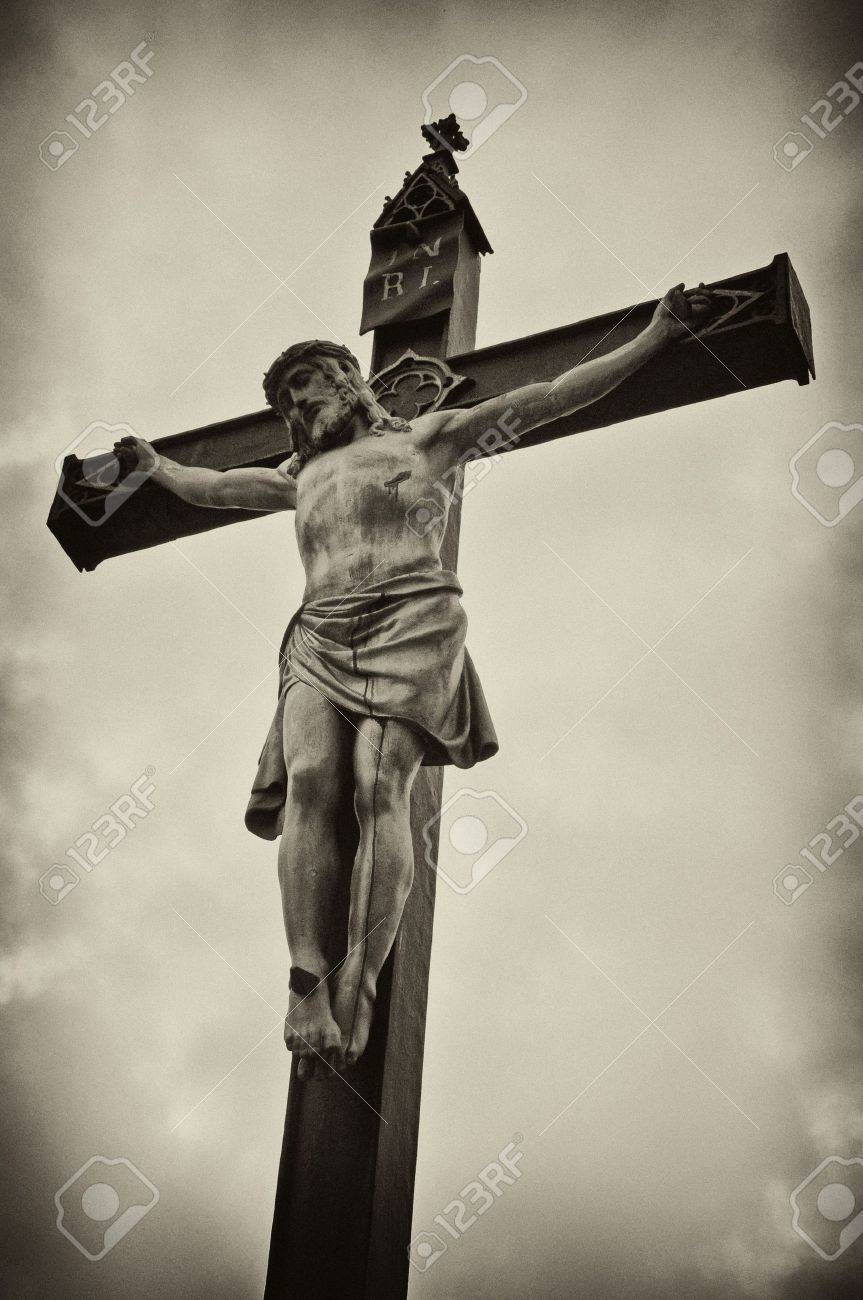 a statue of jesus christ crucified on a cross over a grunge
