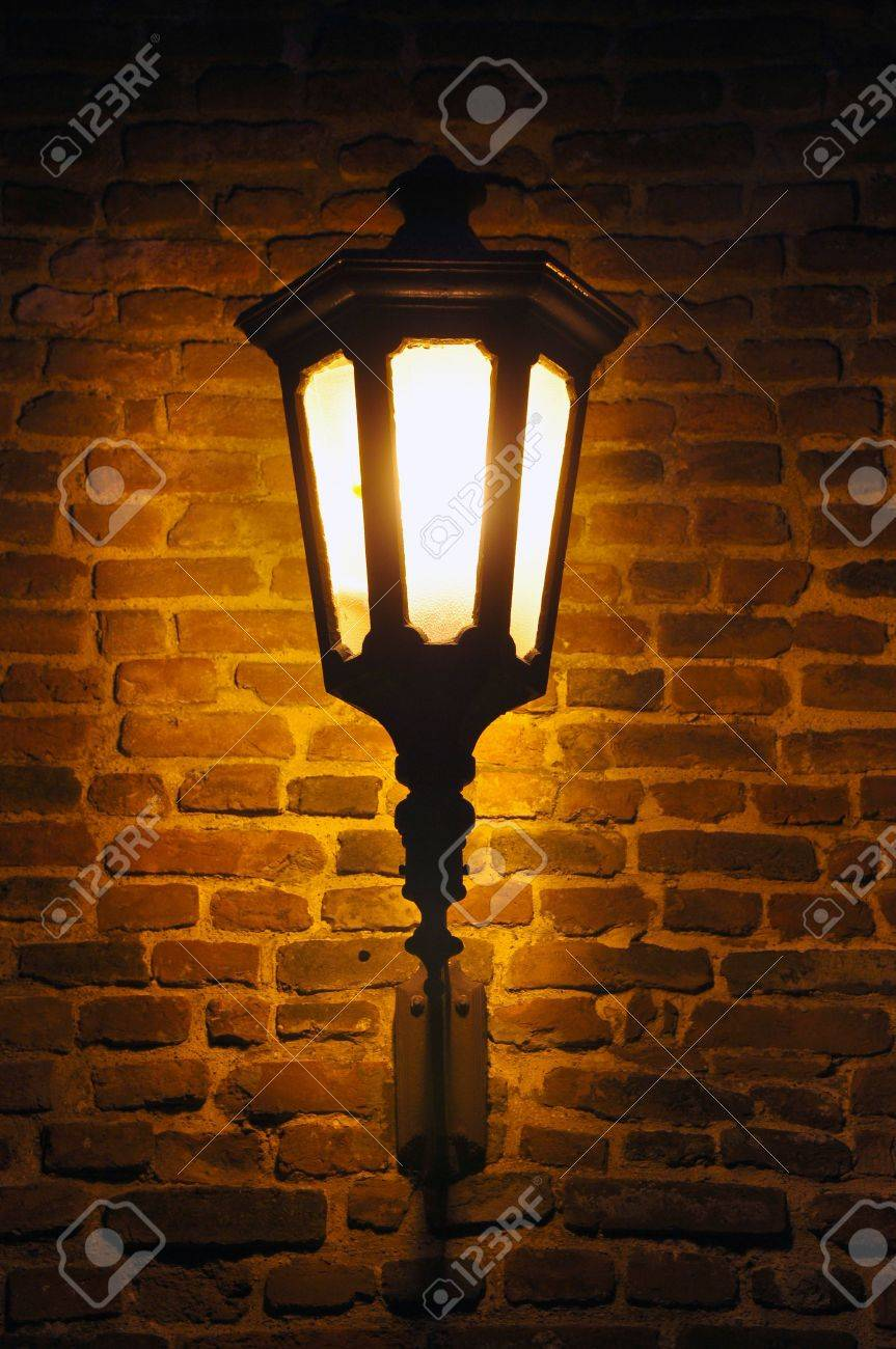 Street Lamp On A Brick Wall Is Lightning In The Dark Stock Photo ...