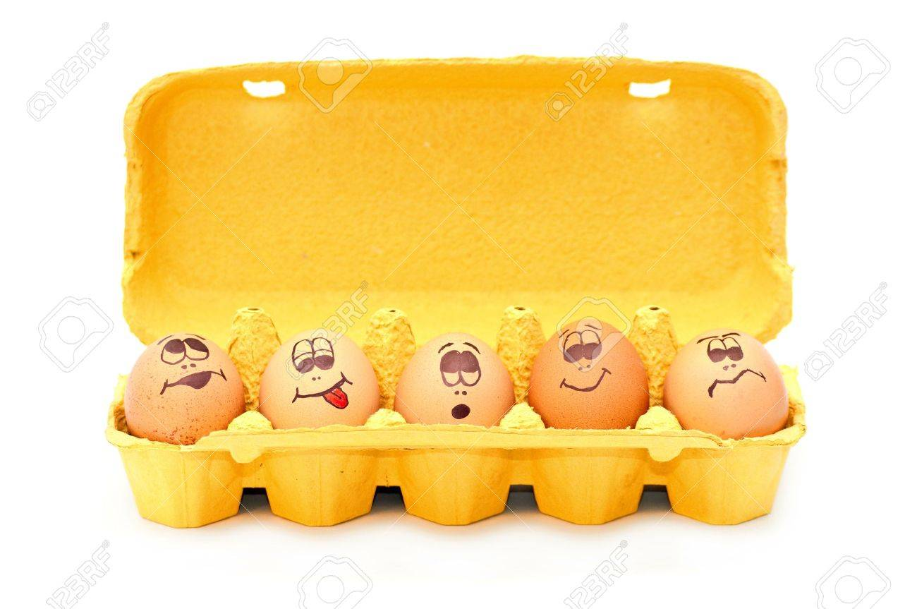 Group of fresh eggs with drawn faces depicting various emotions arranged in a cardboard egg carton against white. Stock Photo - 9095222
