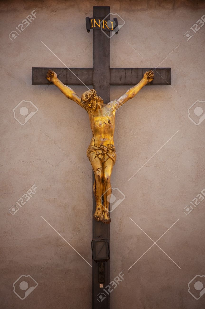 a statue of jesus christ crucified against concrete wall stock