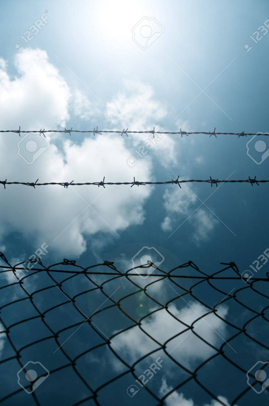 Barbed wire fence against a blue sky with clouds Stock Photo - 11138717