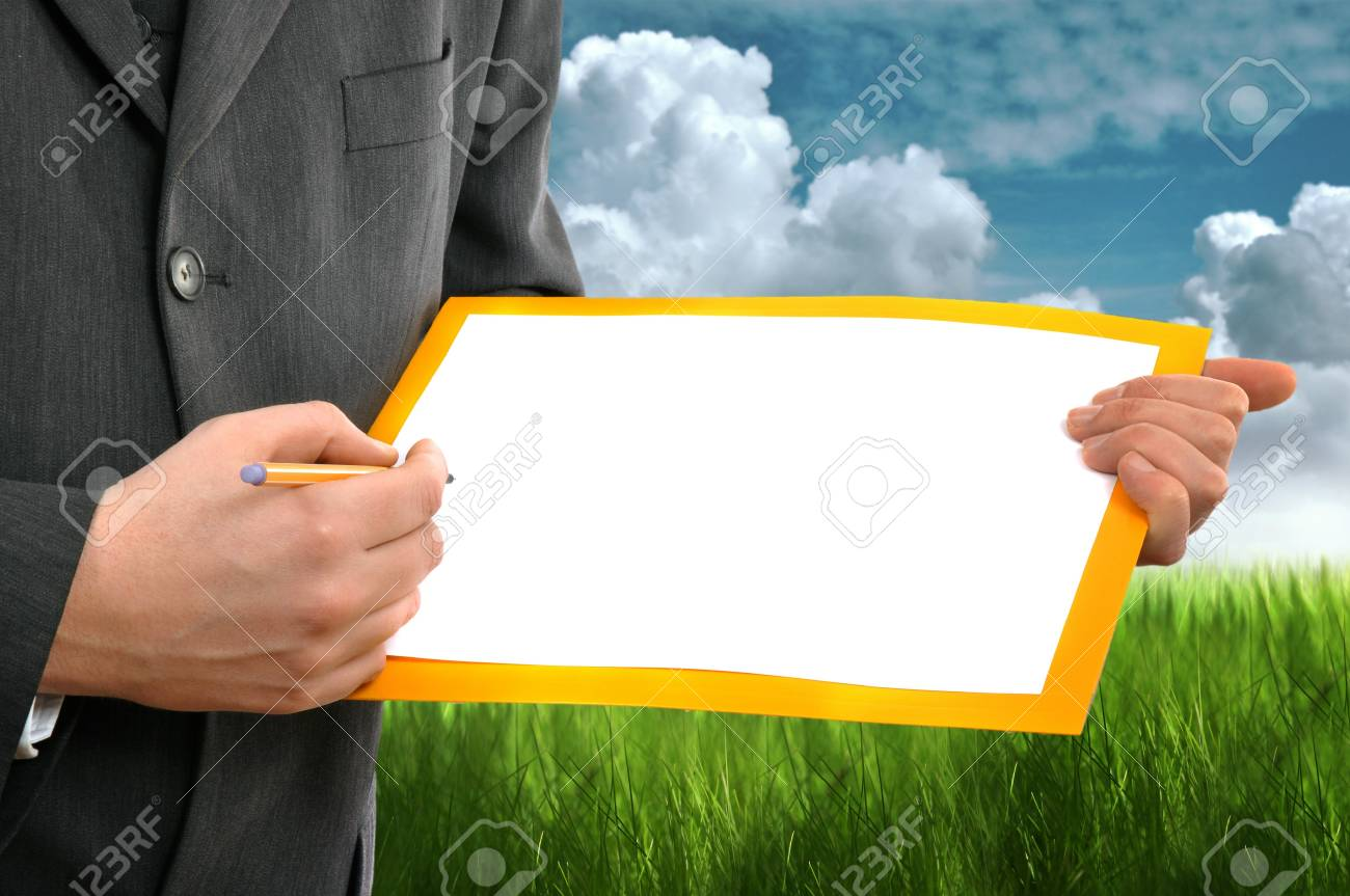 Businessman writing on the blank paper left for copyspace. Green grass and cloudy sky in the background as environmental concept. Stock Photo - 11808091