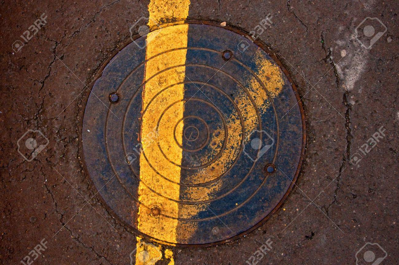 Background or texture  Cast iron sewer manhole lid flush with sidewalk Stock Photo - 13725682