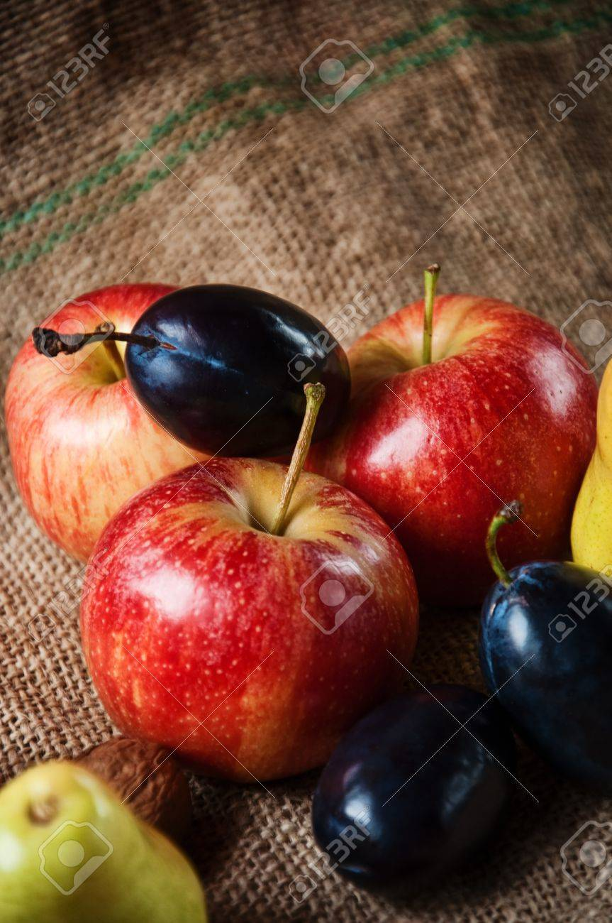 old table full of various fresh autumn fruit apple pear and