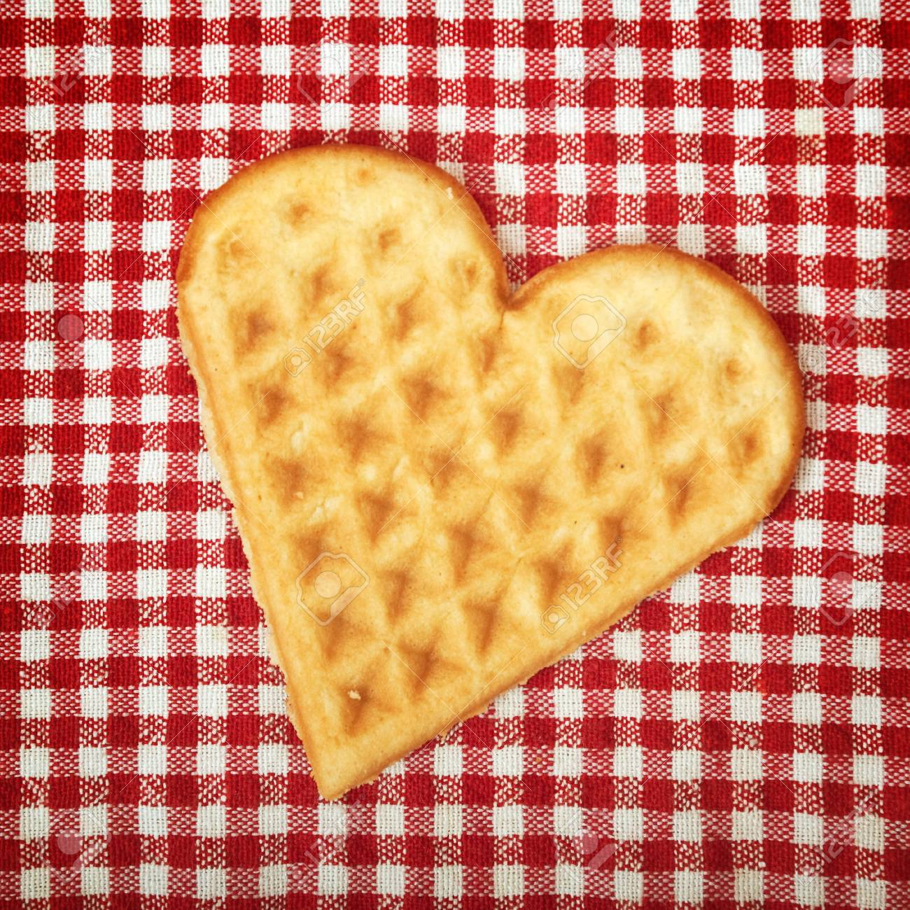 Heart shaped galette cookie on red and white checkered table cloth Stock Photo - 17101990
