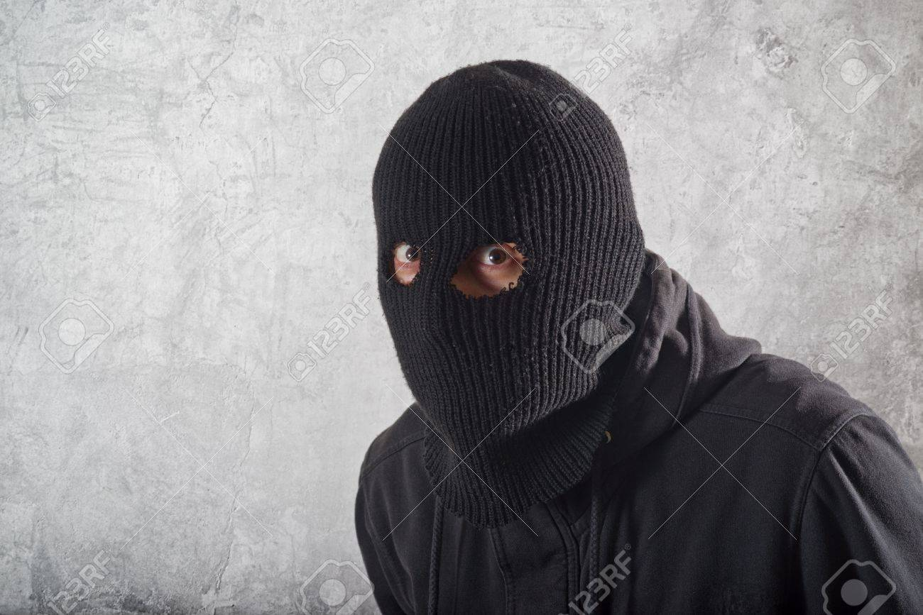 Burglar concept, thief with balaclava caught in front of the grunge concrete wall. Stock Photo - 17687368