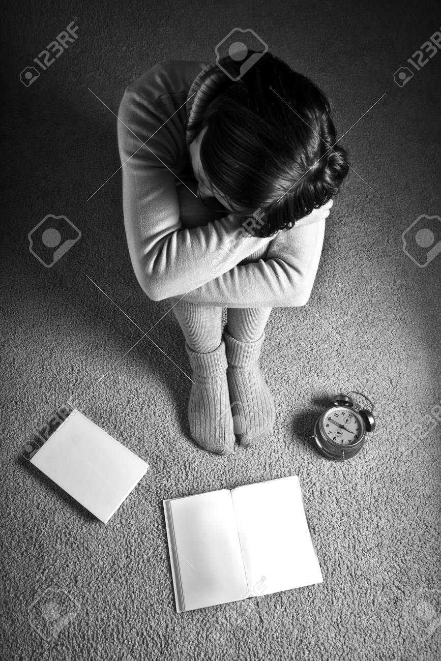 Beautiful young female student sitting on floor in the dark room, anxiously waiting for the exam day Stock Photo - 18547238
