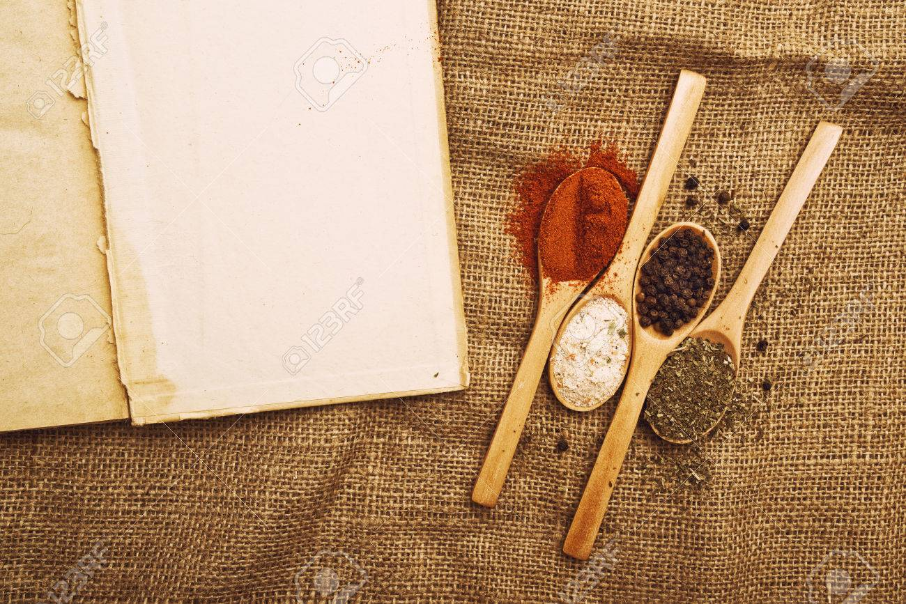 Kitchen Table With Food spices. food ingredients on wood spoons with open book on kitchen