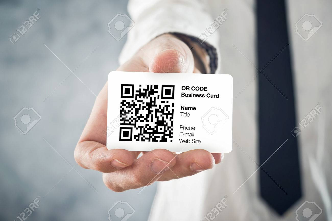 Businessman holding QR code business card with personal data. Modern technology concept. - 27873968