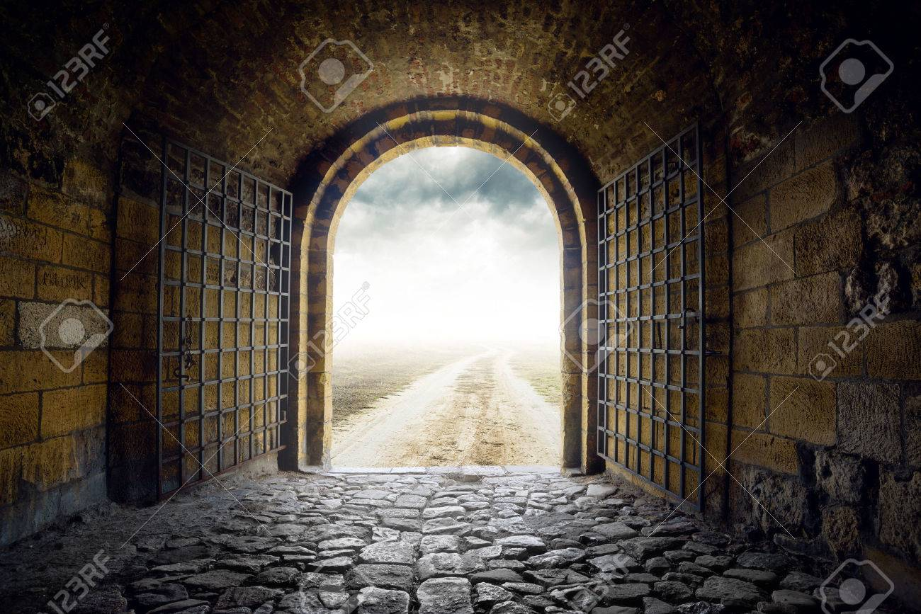 Old Arch Gate opening to endless country road leading nowhere. Hopelessness and great unknown concept. - 31060463