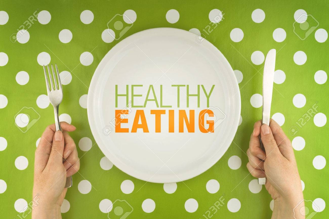 Healthy eating. Woman eating from a white flat plate, top view. - 31197784