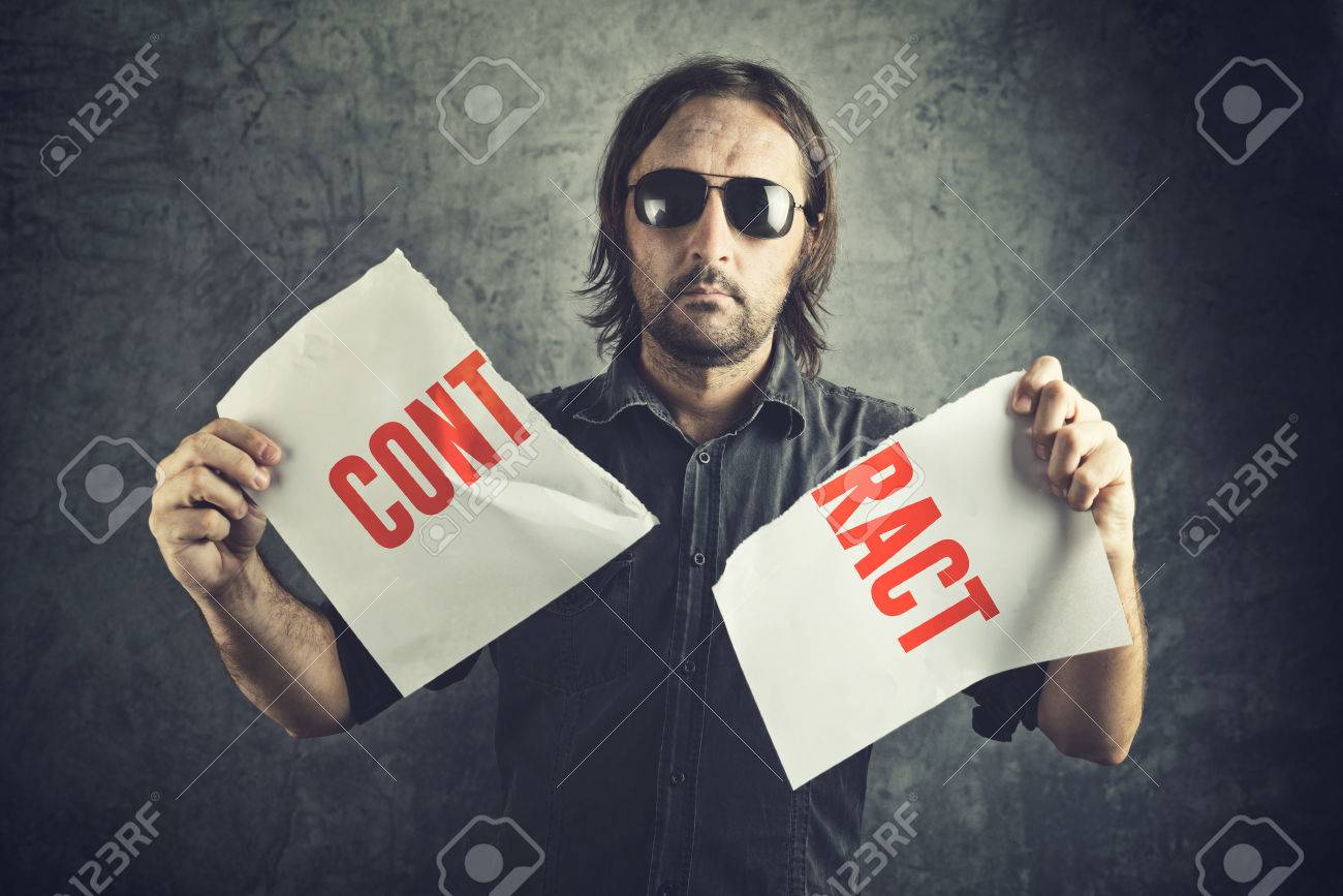 Man tearing apart contract document paper as a gesture of agreement cancellation. - 33150972